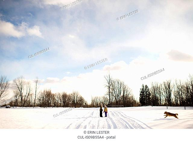 Children on snow-covered path, calling their golden retriever, Lakefield, Ontario, Canada