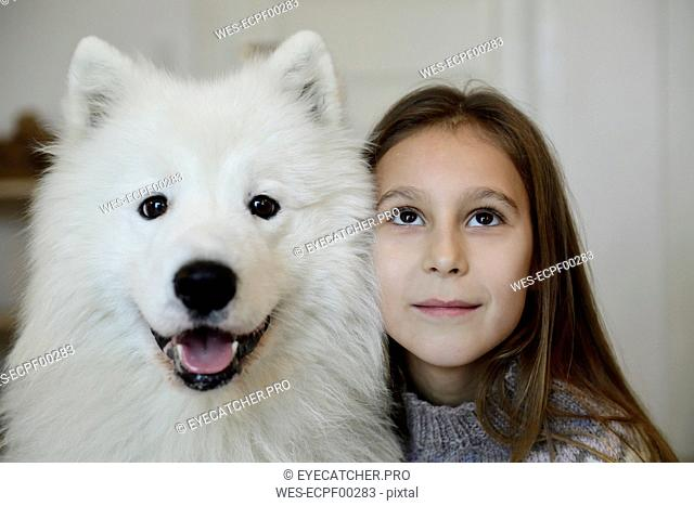 Portrait of girl with her white dog
