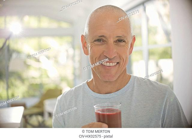 Portrait smiling, confident mature man drinking healthy fruit smoothie