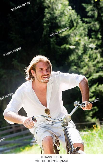 Austria, Salzburg County, Mid adult man riding old bicycle