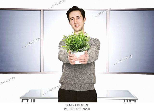 Caucasian businessman holding an office plant in his hands