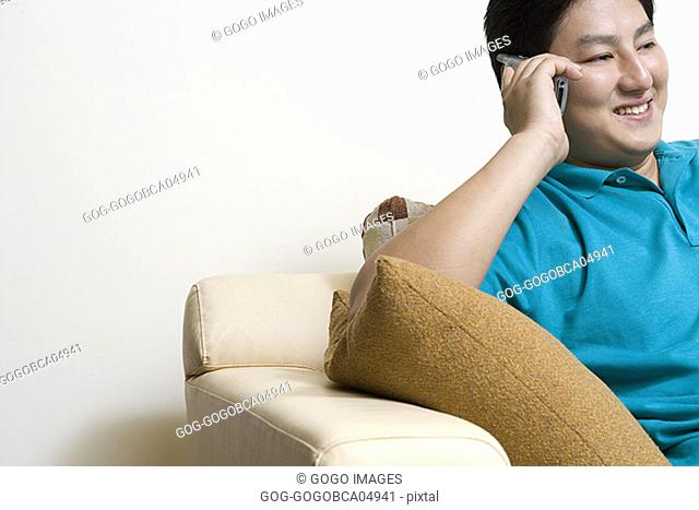 Young man talking on his cell phone on couch