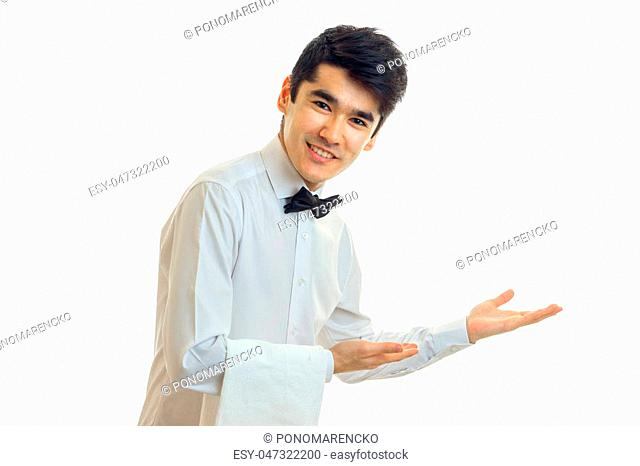 fascinating young waiter with black hair invites guests to the table isolated on a white background close-up