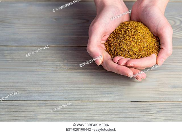 Woman showing handful of milled seed