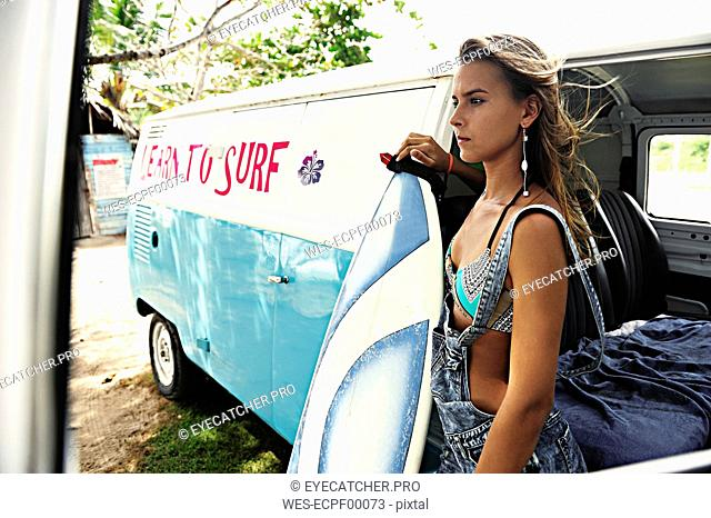 Portrait of woman with surfboard at van