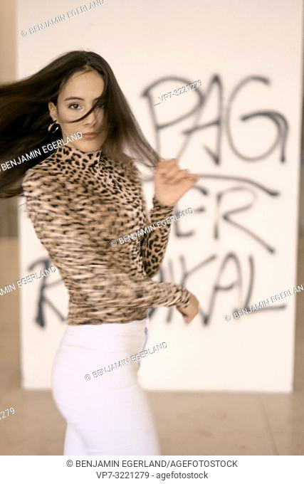 intimate portrait of woman dancing and shaking hair, fashionable clothing style, movement, graffiti, street style, in Munich, Germany
