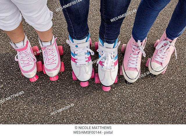 Mother and her two daughters on roller skates, partial view