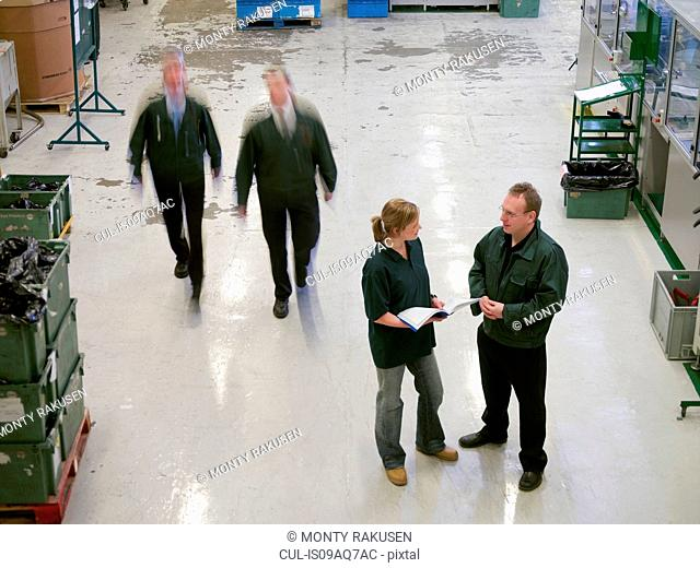 Workers in discussion on factory floor, high angle view