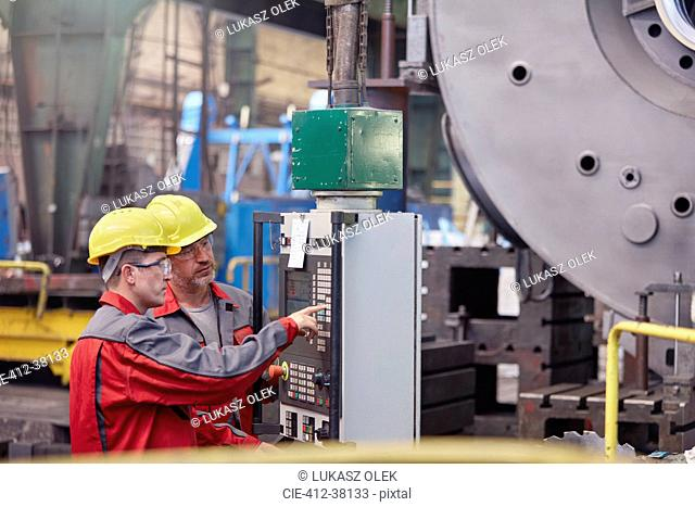 Male workers operating machinery at control panel in factory
