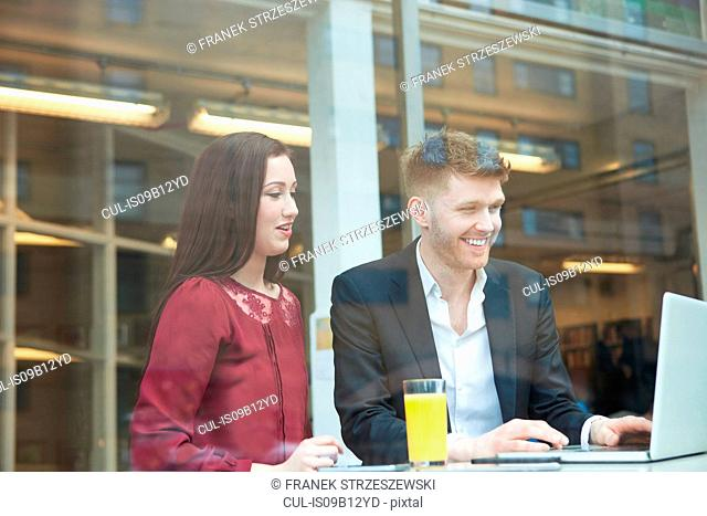 Businesswoman and businessman working with laptop in cafe