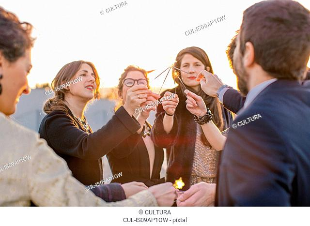 Group of friends lighting sparklers at party