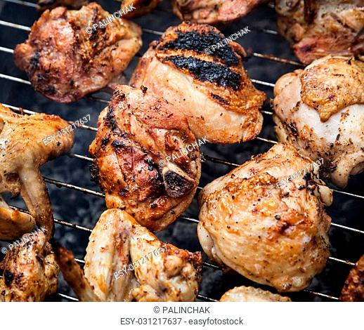 Grilling spiced chicken in grid on charcoal bbq. Shalow DOF