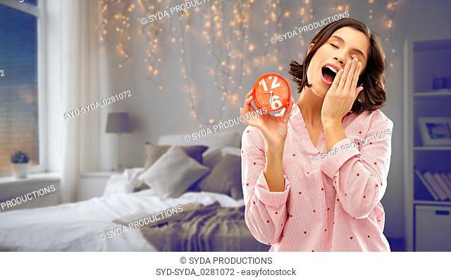 sleepy woman in pajama with alarm clock yawning