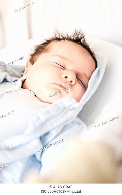 Baby boy sleeping on cot