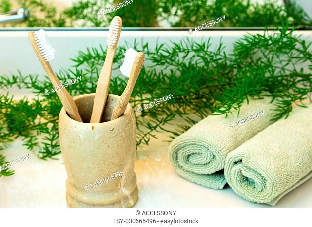 Three bio-degradable, compostable bamboo toothbrushes in marble cup. Rolled green towels in a spa setting. Green plant decor in background