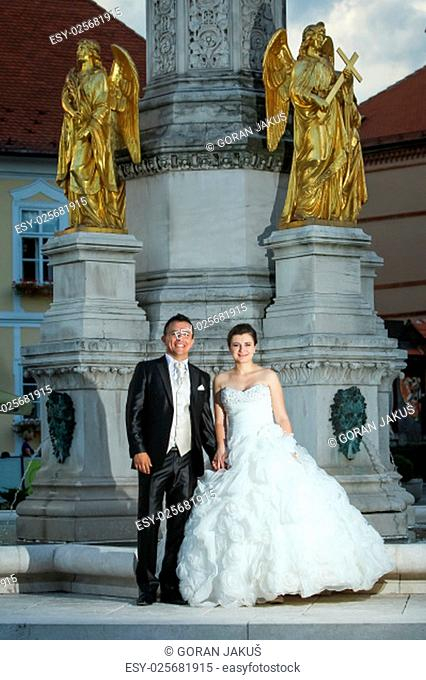 Newlyweds standing in front of the fountain of Virgin mary with four angels and looking at the camera in Zagreb, Croatia