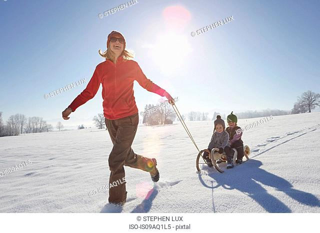 Mother pulling sons along on sled