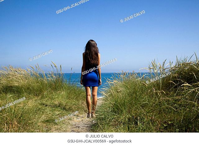 Rear View Portrait of Young Adult Woman Looking out to Sea from Sand Dune with Tall Grasses