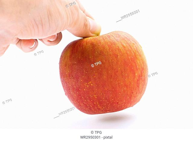 The hand is taking the apple away. Isolated with white background