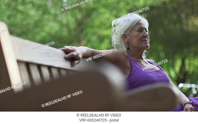 Senior woman relaxing on bench, London, UK