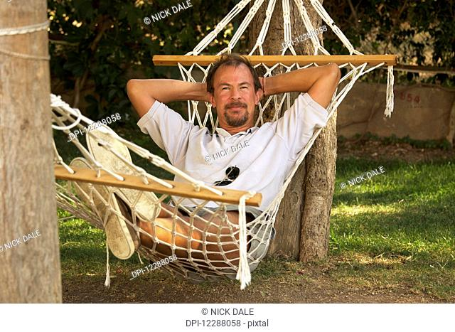 Man laying in a hammock tied to trees; Turkey
