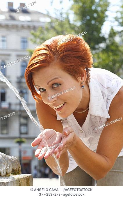 Red hair woman drinking at a fountain