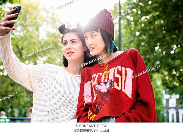 Two young stylish women taking smartphone selfie in city park