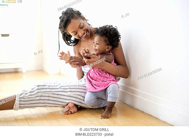 Black woman sitting on floor kissing clapping hands with baby daughter
