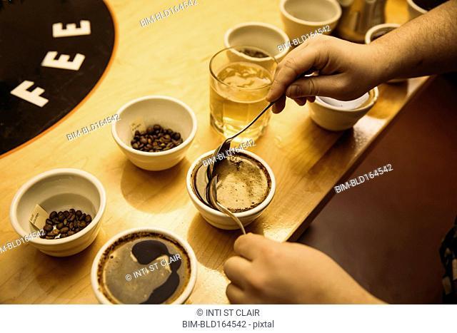 Caucasian barista tasting coffee in coffee shop
