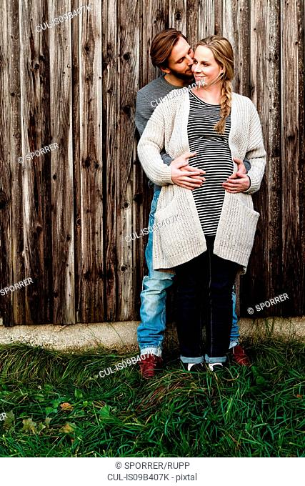 Man kissing pregnant girlfriend on cheek by wooden fence