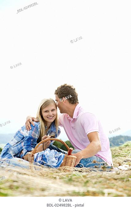 young couple having picnic in field