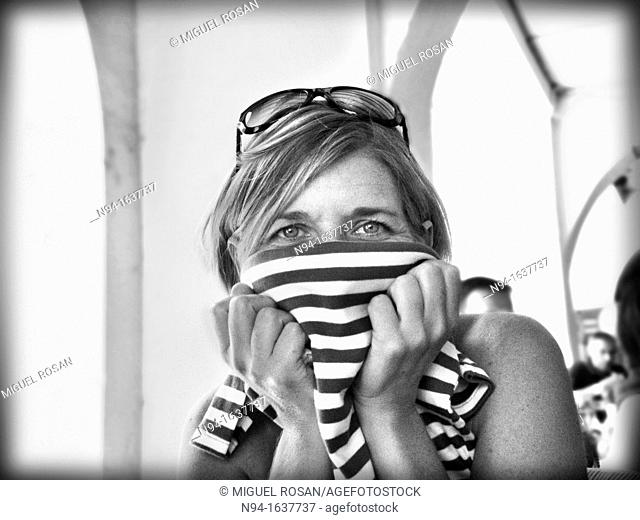 Young blond woman with sunglasses on head, covering her face with a shirt
