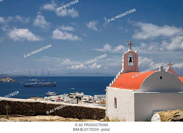 Church overlooking cityscape and ocean, Mykonos, Cyclades Islands, Greece