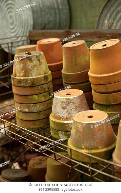 A stack of terra cotta pots on shelves in a garden. Georgia USA