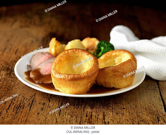 Plate of roast beef, yorkshire puddings, broccoli and potatoes