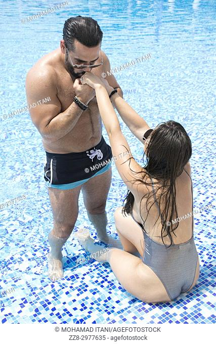 Man kissing his woman's hands in the swimming pool