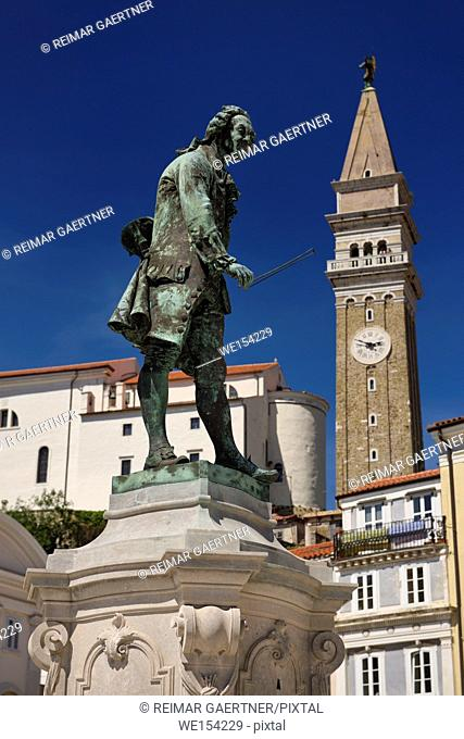 Close up of violinist Giuseppe Tartini statue in Tartini Square Piran Slovenia with St George's Parish church and bell clock tower on blue sky