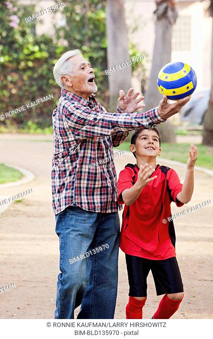 Older Hispanic man and grandson playing with soccer ball