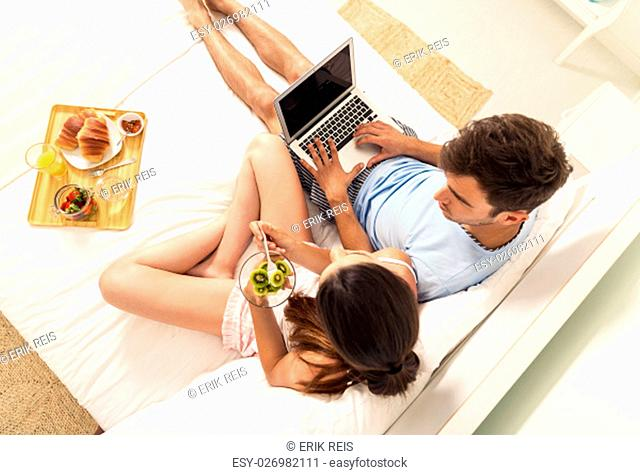 Young couple lying on the bed with breakfast on bed
