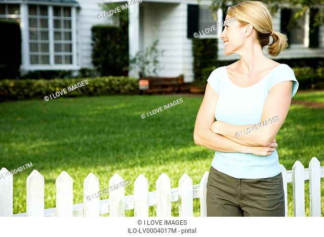 Woman standing by the garden fence outside her new home