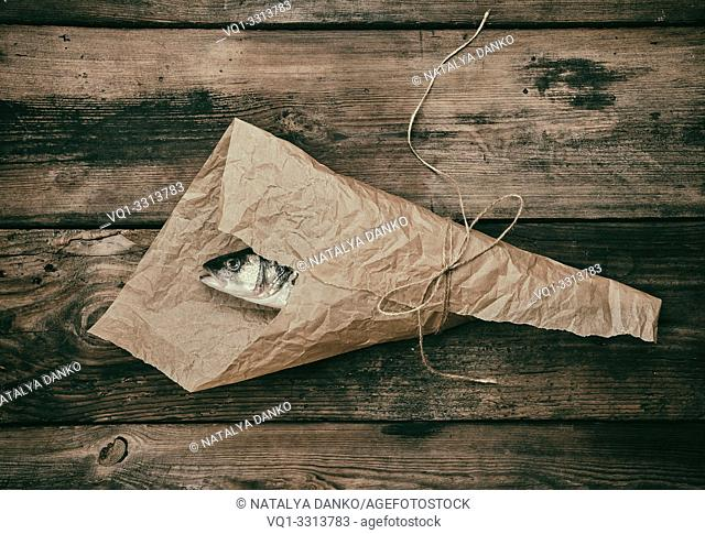 Fresh whole sea bass fish wrapped in a brown paper and tied with a rope, wooden table, top view