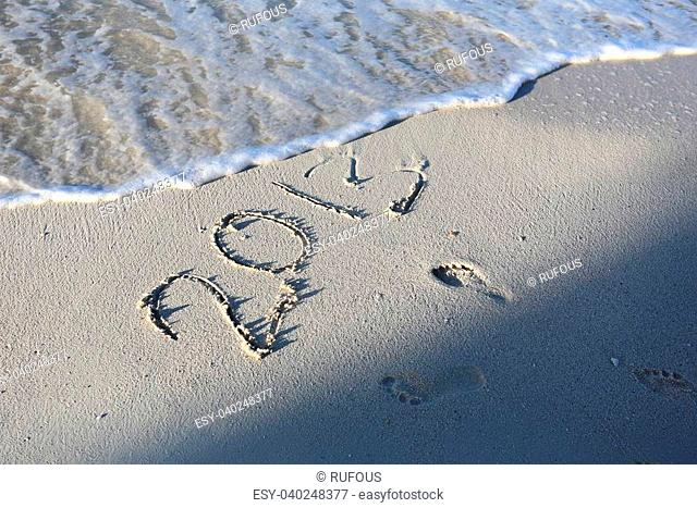 New Year 2014 season is coming concept - inscription 2013 and 2014 on a beach sand
