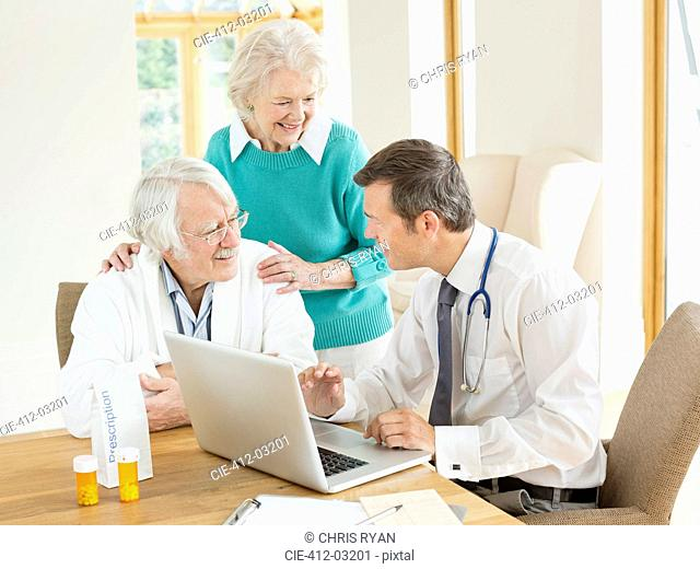 Doctor speaking with older patients at house call