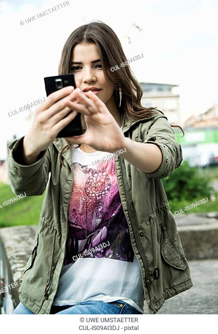 Young woman photographing herself with smartphone