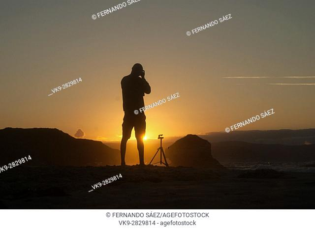 Man taking photos at golden hour in Galicia beach