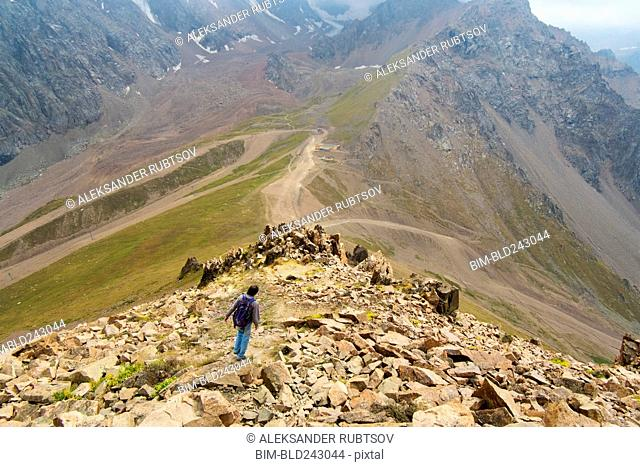 Caucasian man hiking on mountain rocks
