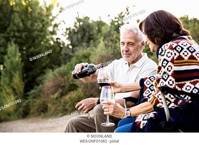 Senior man pouring red wine into glass for his wife