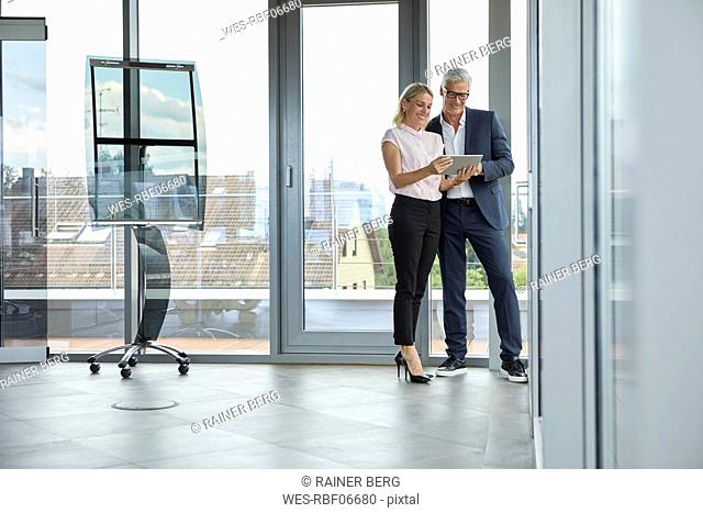 Businessman and woman standing in office, discussing project, looking at digital tabet