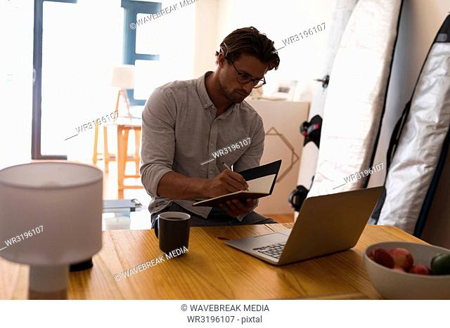 Man writing on a diary while using laptop