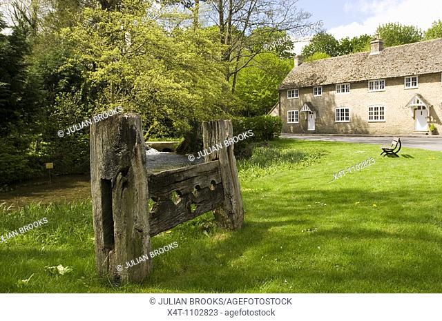 Old wooden stocks at Glympton, near Woodstock, West Oxfordshire  with a bench in the background
